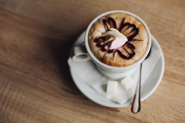 Café quente latte art decorado, café quente mocha decorado em mesa de madeira.