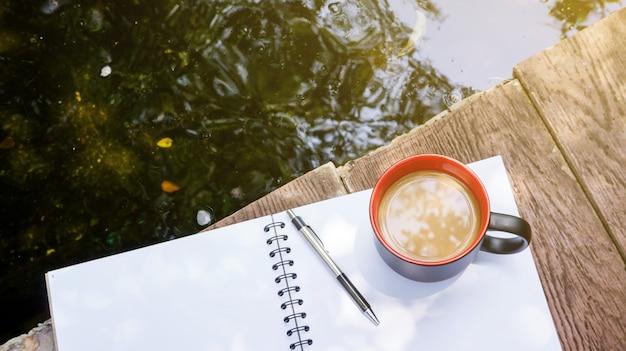Café quente, livro e lugar de caneta perto de uma lagoa.