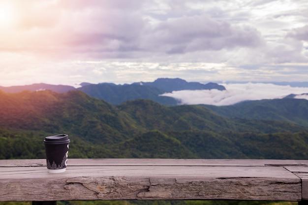 Café quente na mesa de madeira com floresta enevoada no céu da manhã.