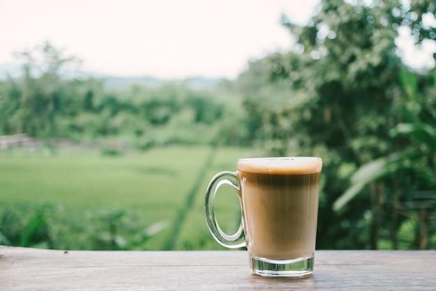 Café quente na mesa de madeira e fundo de visão verde.