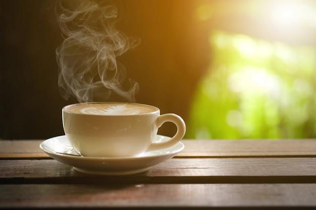 Café quente na mesa de madeira no terraço.
