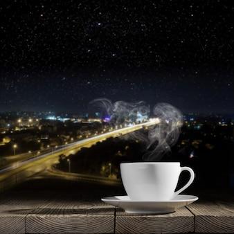 Café quente na mesa em um fundo de cidade à noite