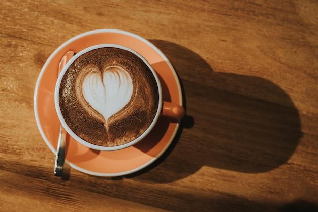 Café quente no copo no foco macio da tabela de madeira, efeito retro tonificado.