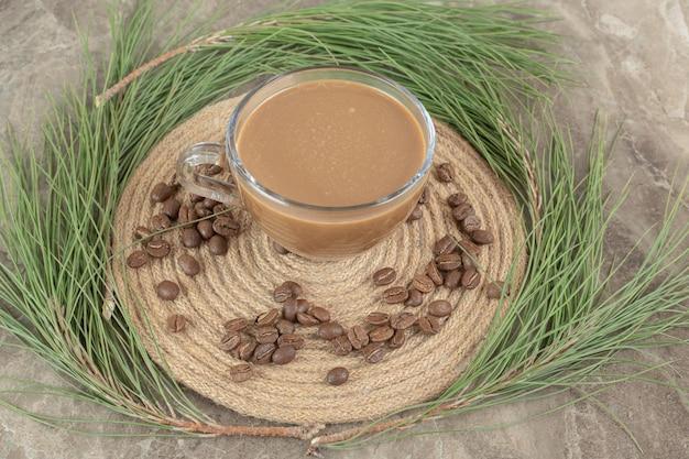 Café quente, pinheiro e grãos de café na peça de madeira