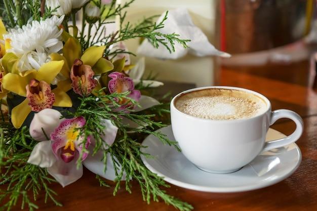 Café quente, pronto para beber em uma xícara de café, colocado ao lado de um vaso de flores