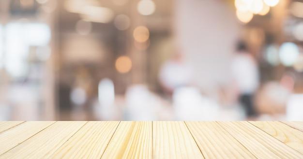 Café restaurante ou cafeteria com luzes abstratas bokeh fundo desfocado com mesa para exposição de produtos