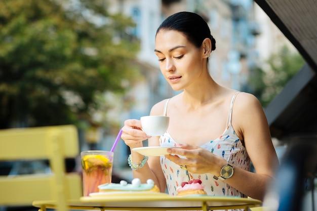 Café saboroso. mulher jovem e bonita e relaxada sentada em um terraço de café segurando uma xícara de café quente