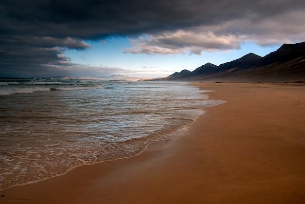 Café selvagem e celestial da praia no sul de fuerteventura com nuvens. ilhas canárias. espanha