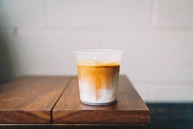 Café sujo em copo para viagem na mesa de madeira