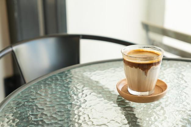 Café sujo - um copo de café expresso misturado com leite fresco frio em uma cafeteria e restaurante