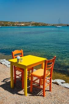 Cafe tableon beach na cidade de adamantas, na ilha de milos, com o mar egeu e barcos ao fundo