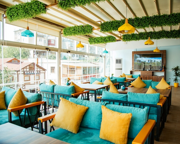 Café terraço com sofás turquesas e almofadas amarelas