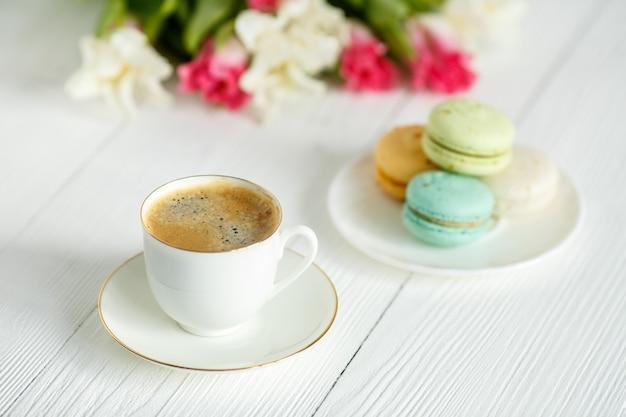 Café, tulipas cor de rosa e brancas e macarons na mesa de madeira branca. café da manhã. pausa para o café.