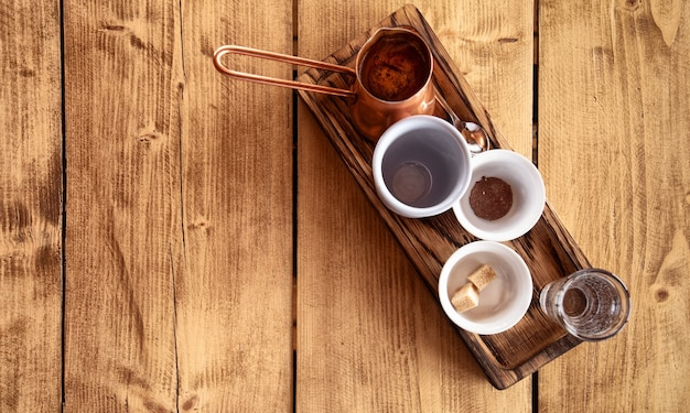 Café turco clássico. bandeja de madeira, xícara de café, chocolate, biscoitos e turco de cobre em uma mesa de madeira.