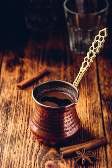Café turco com canela e anis. café moído em cezve de cobre sobre superfície de madeira
