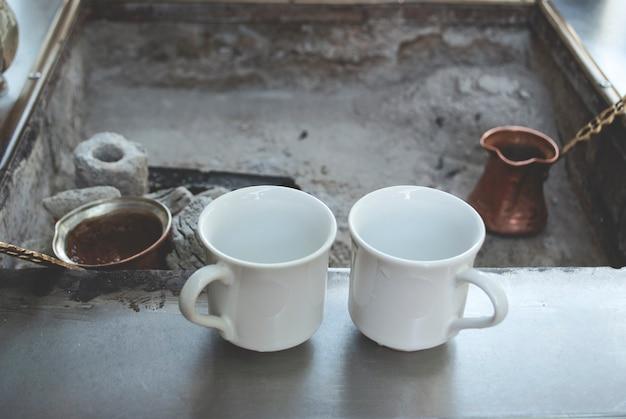 Café turco com carvão. o café está sendo feito na brasa em uma cezve de café turco. duas xícaras estão na superfície perto das brasas.