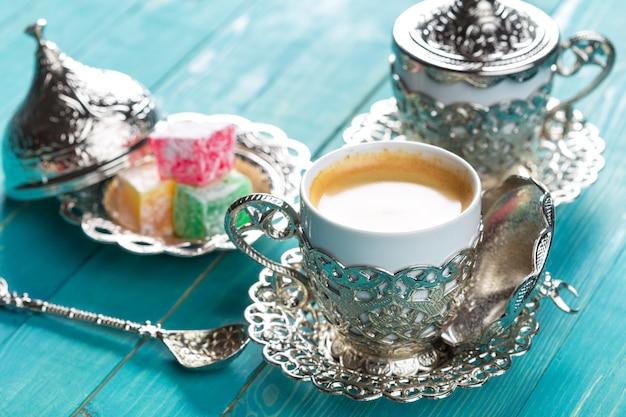 Café turco tradicional e manjar turco na mesa de madeira.