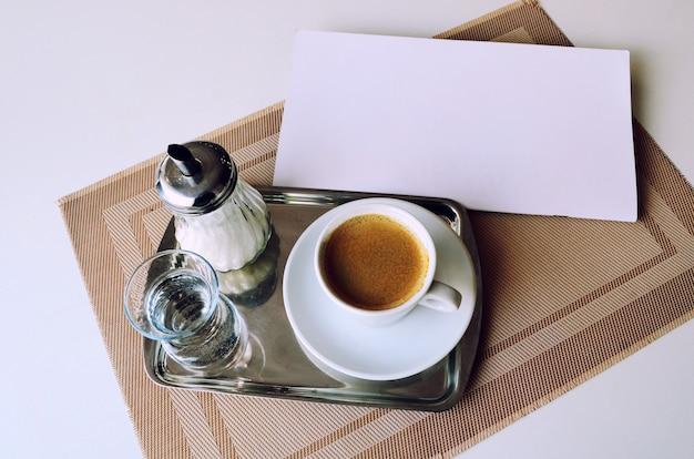 Café, um copo de água e açúcar em uma bandeja de ferro.