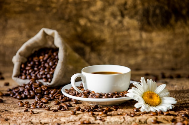 Café. uma xícara de café quente e grãos de café torrados na madeira