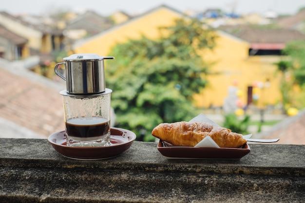 Café vietnamita e croissant em cima da mesa