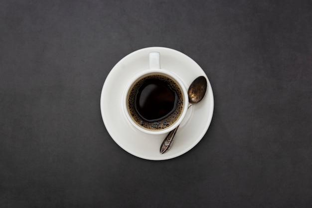 Café. xícara de café branca vista superior colher e prato em fundo escuro