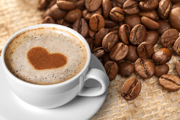 Cafés e restaurantes. uma caneca de café preto com espuma e grãos de café.