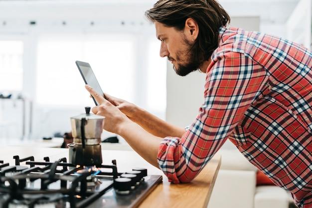 Cafeteira clássica no fogo de gás com um homem que olha a tabuleta digital na cozinha