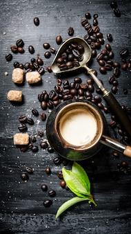 Cafeteira com grãos de café, açúcar de cana e folhas frescas. em um quadro negro.