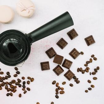 Cafeteira com pedaços de chocolate e grãos de café torrados e marshmallow