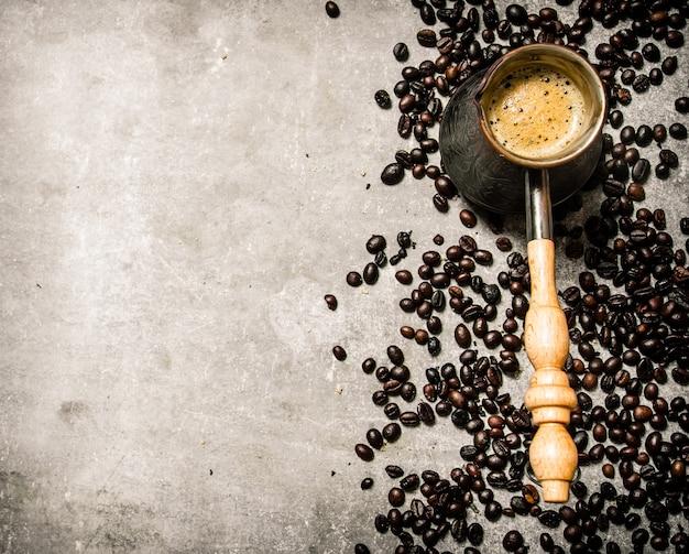 Cafeteira e café torrado ao redor. sobre um fundo de pedra.