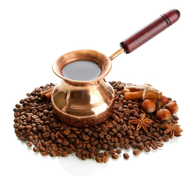Cafeteira e grãos de café, isolados no branco