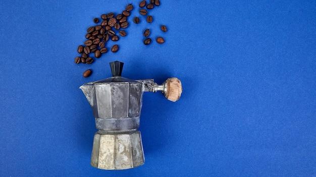 Cafeteira e grãos de café sobre fundo azul tendência