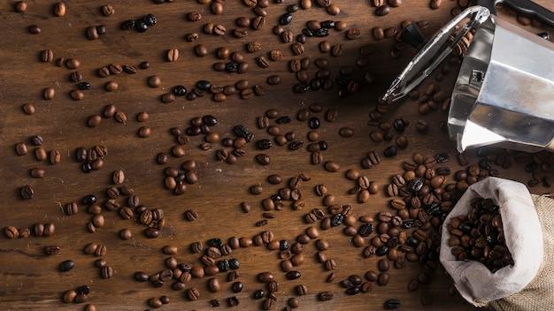 Cafeteira e saco com grãos espalhados