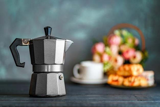 Cafeteira mocha, flores e doces na superfície escura para a hora do café