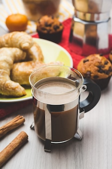 Cafeteira, muffins, croissant e xícara de café