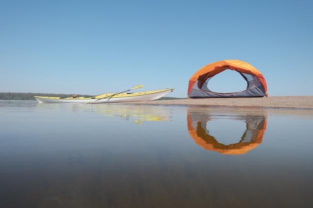 Caiaque de mar atracado na costa. tenda aberta na costa