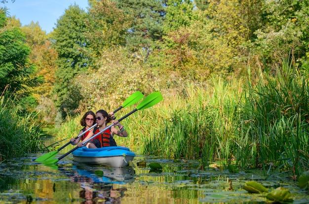 Caiaque em família, mãe e filha remando em caiaque no passeio de canoa no rio se divertindo, fim de semana ativo de outono e férias com crianças, conceito de aptidão