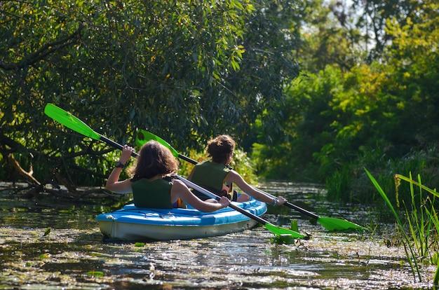 Caiaque em família, mãe e filha remando em caiaque no passeio de canoa no rio se divertindo, fim de semana ativo de outono e férias com crianças, conceito de fitness