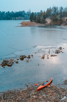 Caiaque encontra-se em uma praia selvagem de um lago selvagem