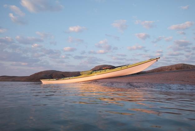 Caiaque marítimo atracado na costa de granito. tópicos de turismo ativo
