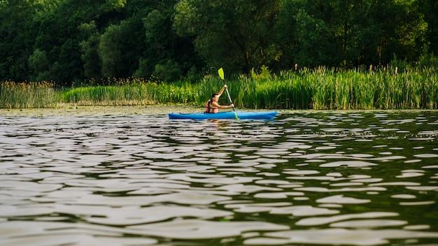 Caiaque masculino com remo na superfície da ondinha da água