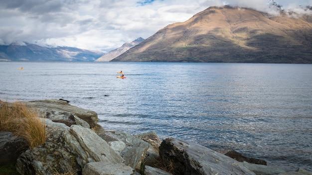Caiaque no lago cercado por montanhas, foto de paisagem feita em queenstown, nova zelândia