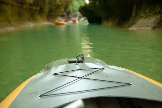 Caiaque no rio. grupo de pessoas em um barco navegando ao longo do rio.