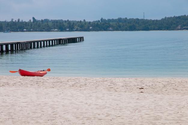 Caiaque vermelho na praia com mar tropical