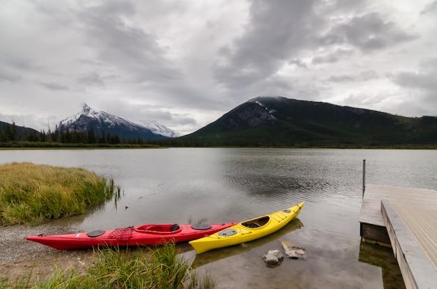 Caiaques vermelhos e amarelos que sentam-se por uma doca com uma vista do monte rundle em lagos vermillion
