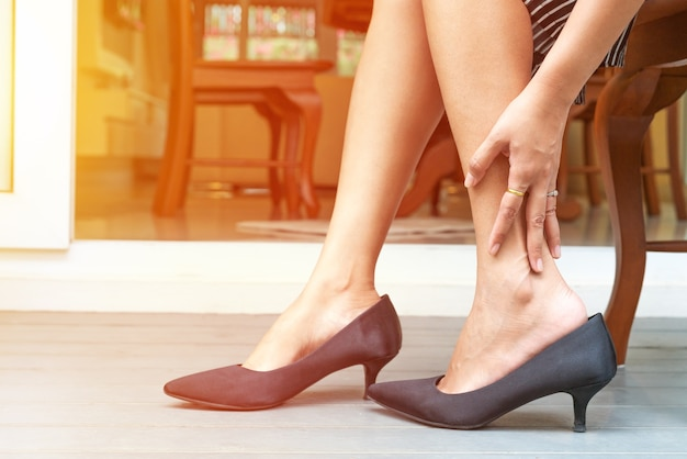 Cãibra de perna de mulher de usar sapatos de salto alto, conceito de saúde