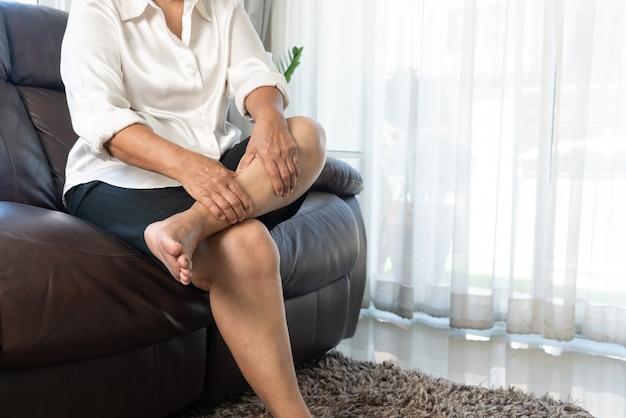 Cãibra nas pernas, mulher idosa com cãibras nas pernas em casa, conceito de problema de saúde