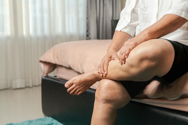 Cãibra nas pernas, mulher idosa sofrendo de cãibras nas pernas em casa, conceito de problema de saúde