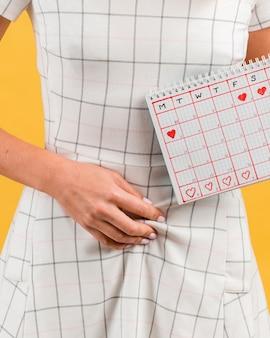 Cãibras no estômago e close-up do calendário do período