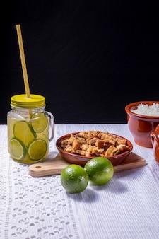 Caipirinha brasileira, coquetel típico brasileiro feito com limão, cachaça e açúcar e barriga de porco crocante frita.